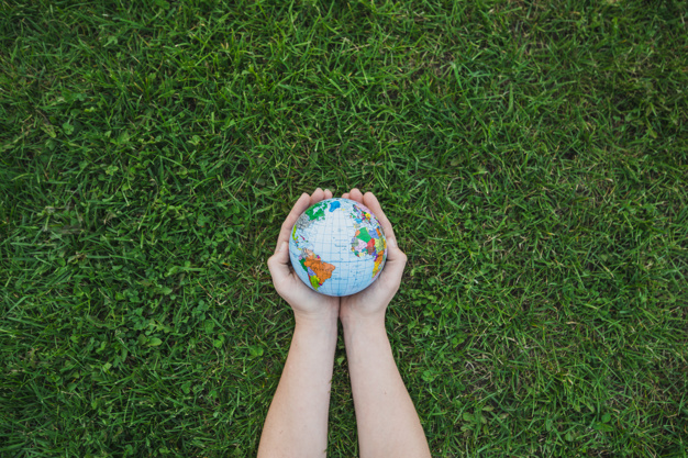 an-overhead-s-view-of-hands-holding-globe-over-green-grass_23-2147817206